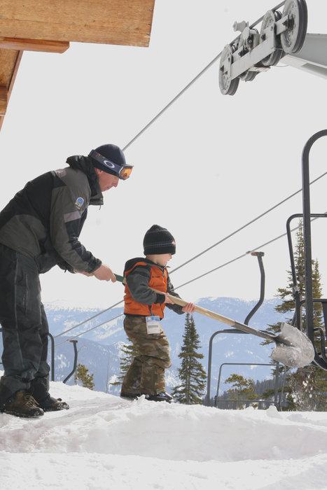 A kid shovels snow at Big Sky Resort, Montana