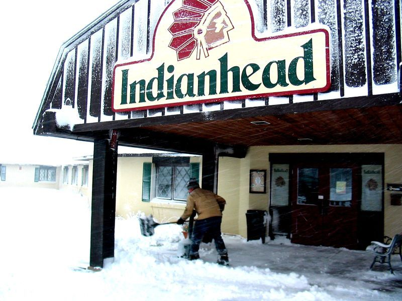 An Indianhead Mountain, Michigan employee shovels snow in the entrance to Indianhead Mountain
