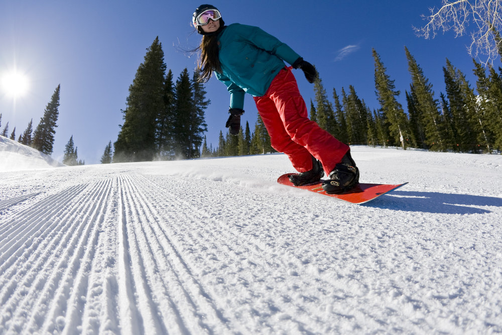 A snowboarder shreds the corduroy on Aspen Mountain.