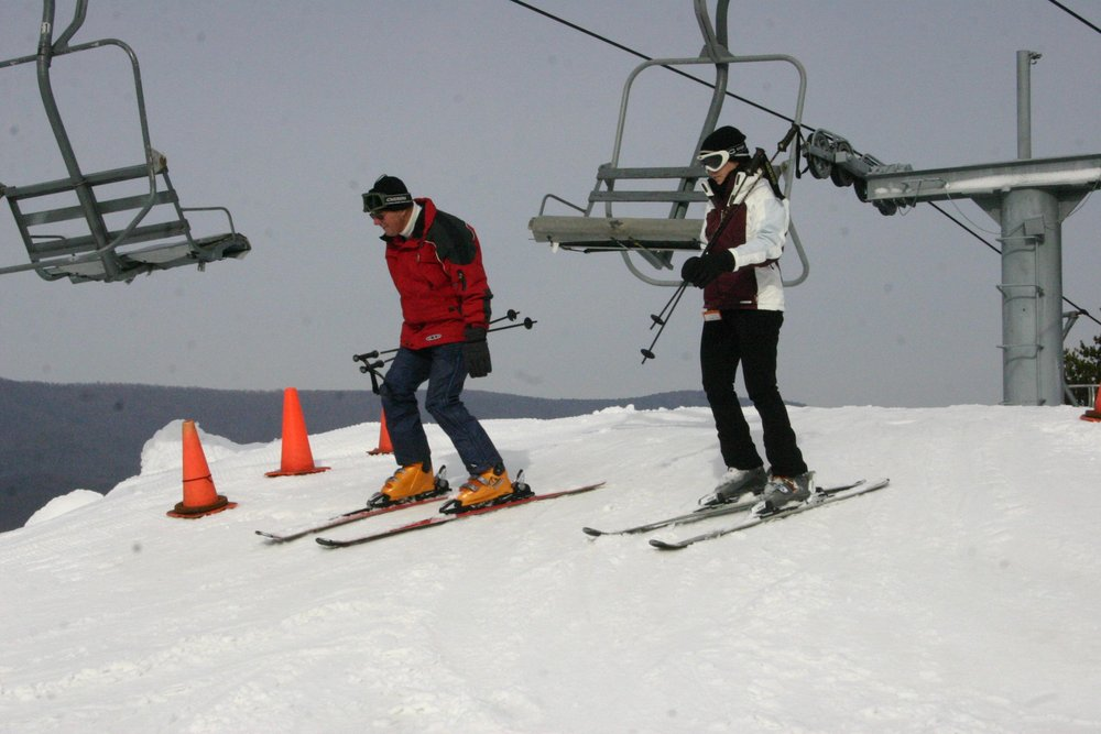 Two skiers get off a chair lift at Bryce Resort, Virginia
