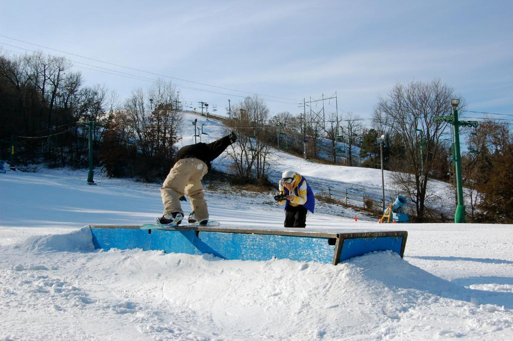 A snowboarder rides a rail in the terrain park at Afton Alps, Minnesota