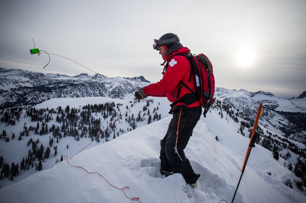 Joe Calder tosses a charge approximately 20 meters down the north face of Peaked Mountain attached to rope so it would tumble down the face prior to detonating. - ©Cody Downard Photography