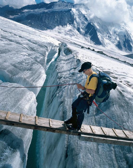 Switzerland. get natural. The crossing of a crevasse during a guided hiking tour on the Aletsch Glacier in Canton Valais. Schweiz. ganz natuerlich. Das Ueberqueren einer Gletscherspalte waehrend einer gefuehrten Wanderung auf dem Aletschgletscher im Kanton Wallis. Suisse. tout naturellem