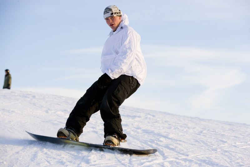 A snowboarder makes a turn on the mountain, Shanty Creek Resorts, Michigan