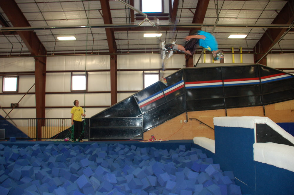 Young skier about to land in the Barn's foam pit at Woodward at Copper.
