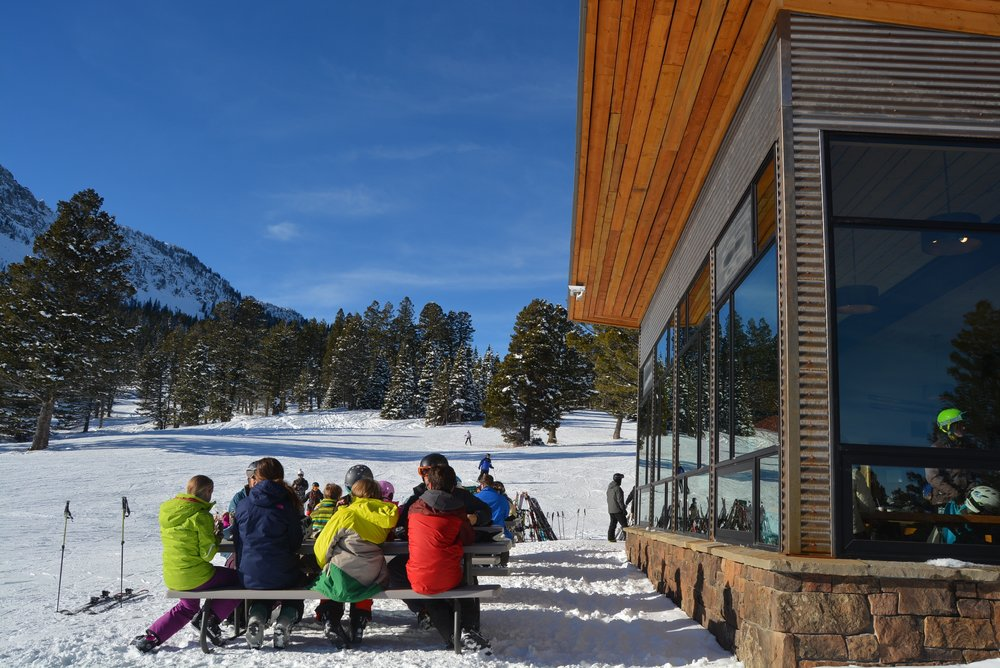 Family enjoys lunch in the sun and snow in front of New Alpine Cabin - ©Bridger Bowl
