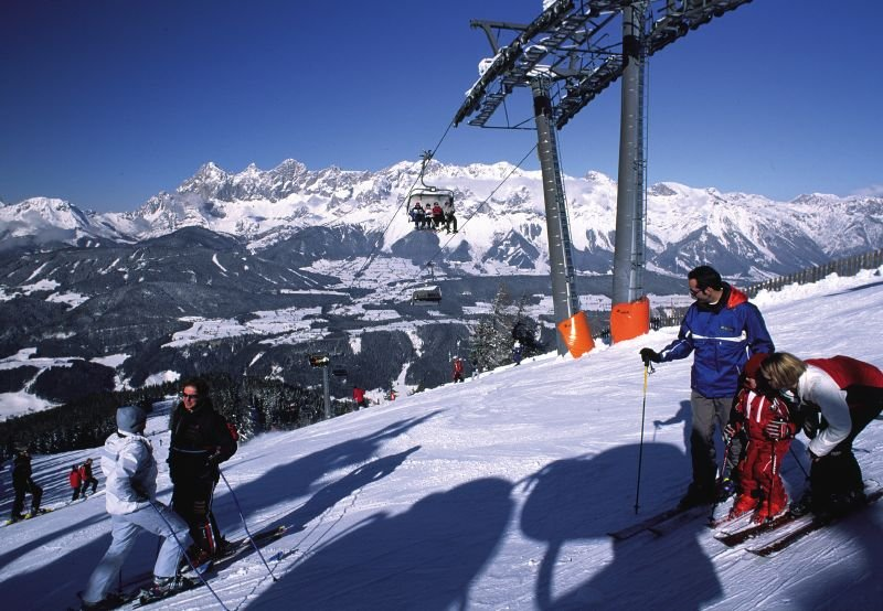 Skiers by a lift tower at Schladming AUT