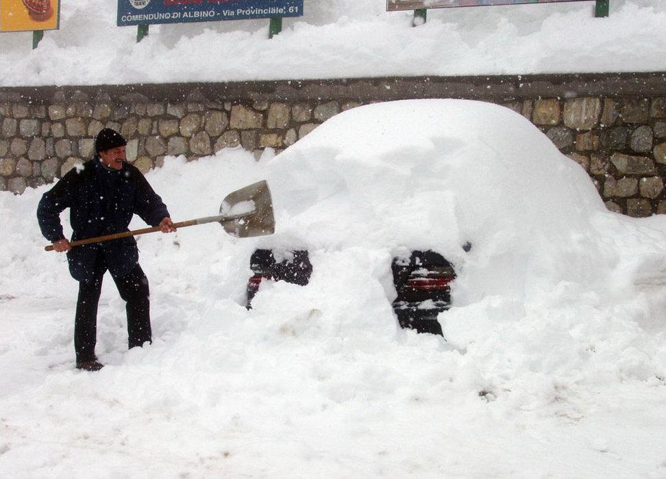 Man shoveling snow at Foppolo, Italy.