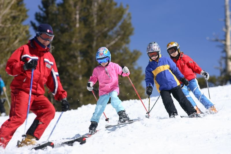 A ski school instructor teaches three young skiers at Heavenly Mountain Resort in South Lake Tahoe, California