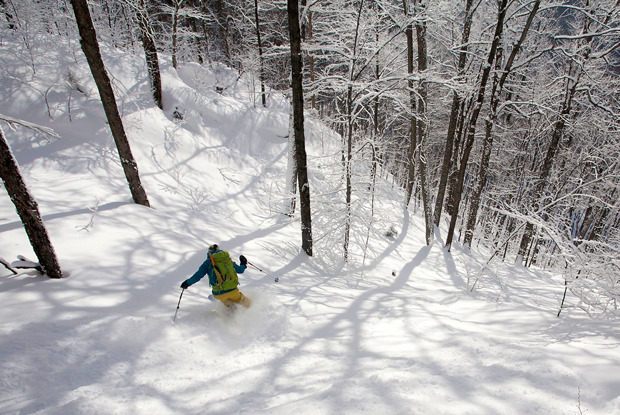 Skier Emily Johnson skis fresh snow in the morning light of the Bolton backcountry. Photo by Brian Mohr.