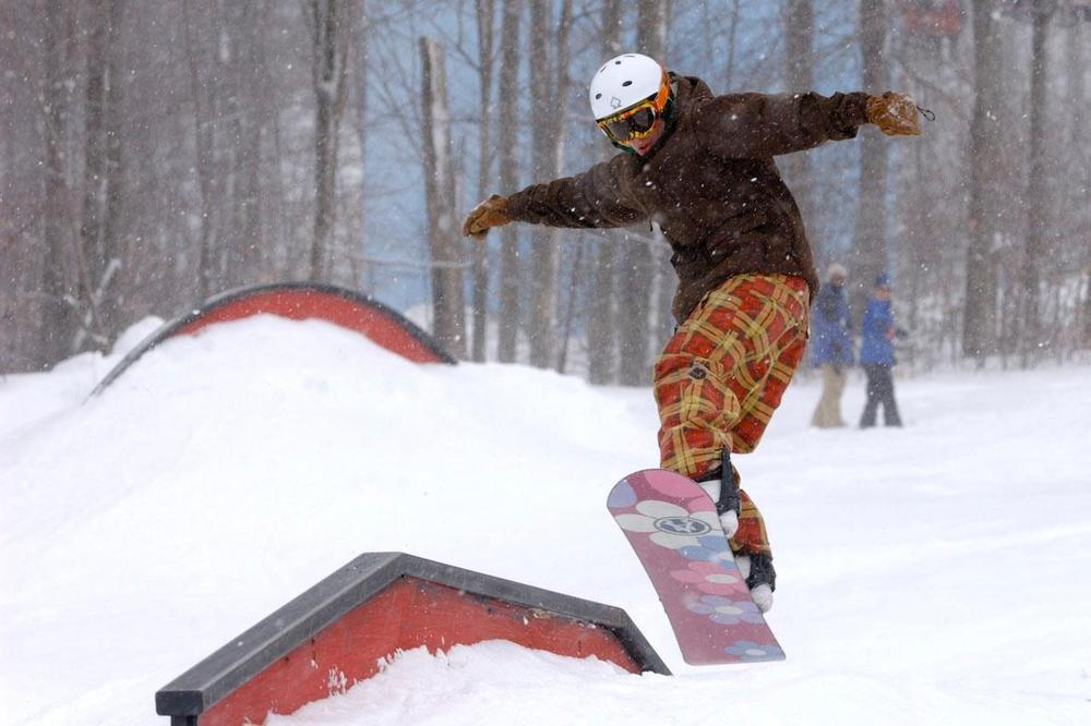 A snowboarder launches onto a rail in the Timberline Park. Photo Courtesy of Timberline Resort.