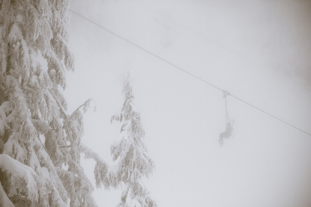 A lone snowboarder rides up the mountain through the fog