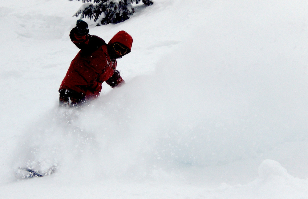 A snowboarder sinks into Grand Targhee powder. Photo by Rob Baird/Flickr.