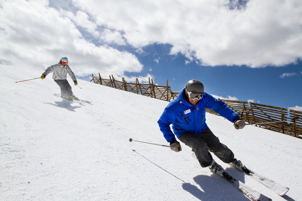 An instructor with the Winter Park Ski & Ride School leads students down a run.