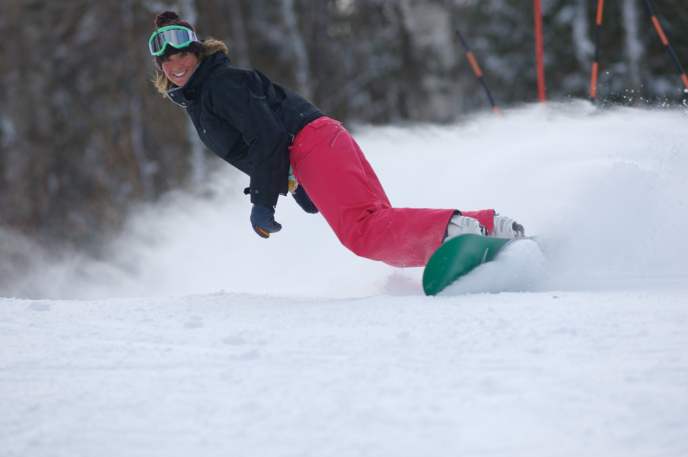 A female snowboarder at Mount Sunapee throws up a cloud of powder as she makes a hard carve.