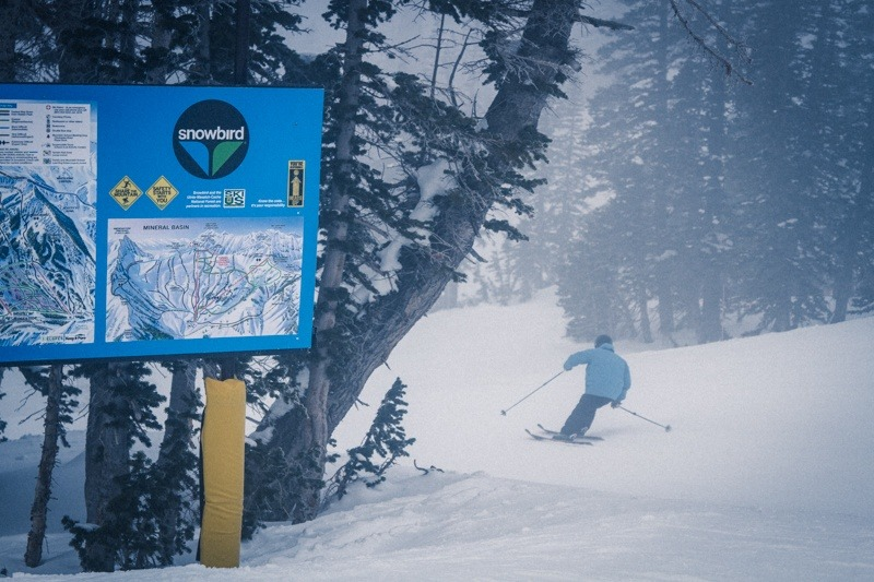 Testing frontside skis with the Snowbird Trail Map in the background.