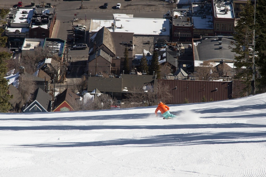 Park City local and retired pro skier Meghan Brown rips it up at Park City Mountain Resort. From several groomers on the mountain you can see town down below. - ©Liam Doran