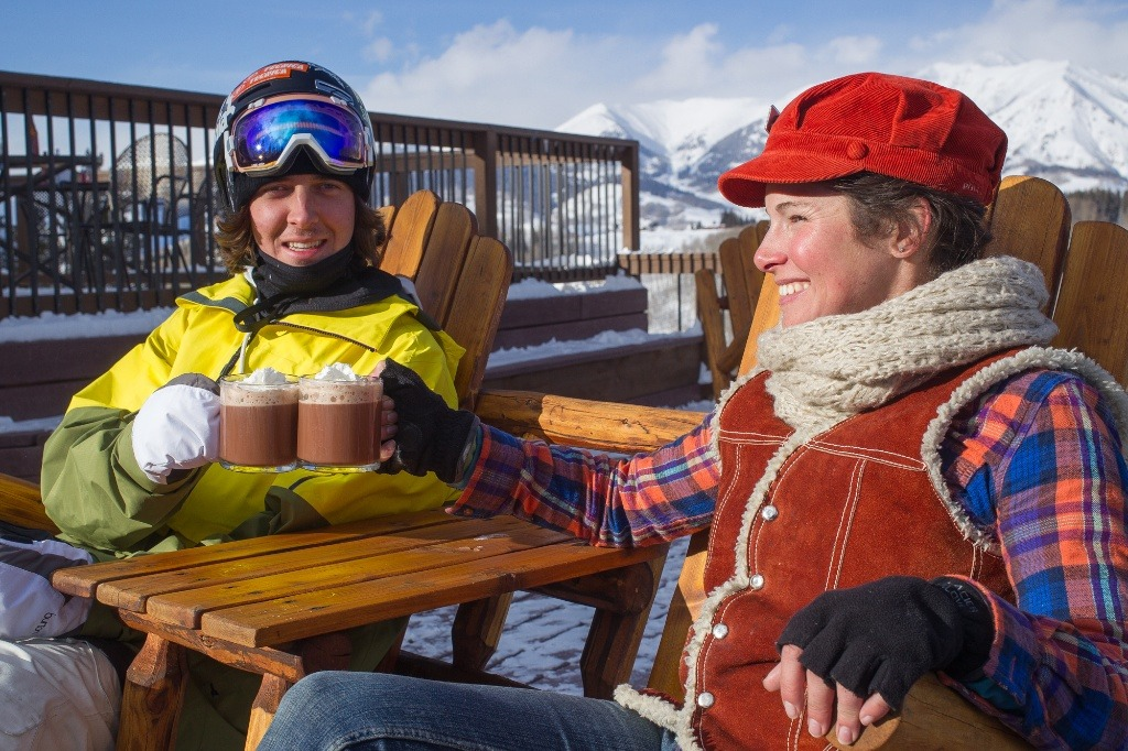 Aidan Sheahan and Crested Butte local, Sarah Joy enjoy a cup of hot coco on a deck on Crested Butte Mountain.