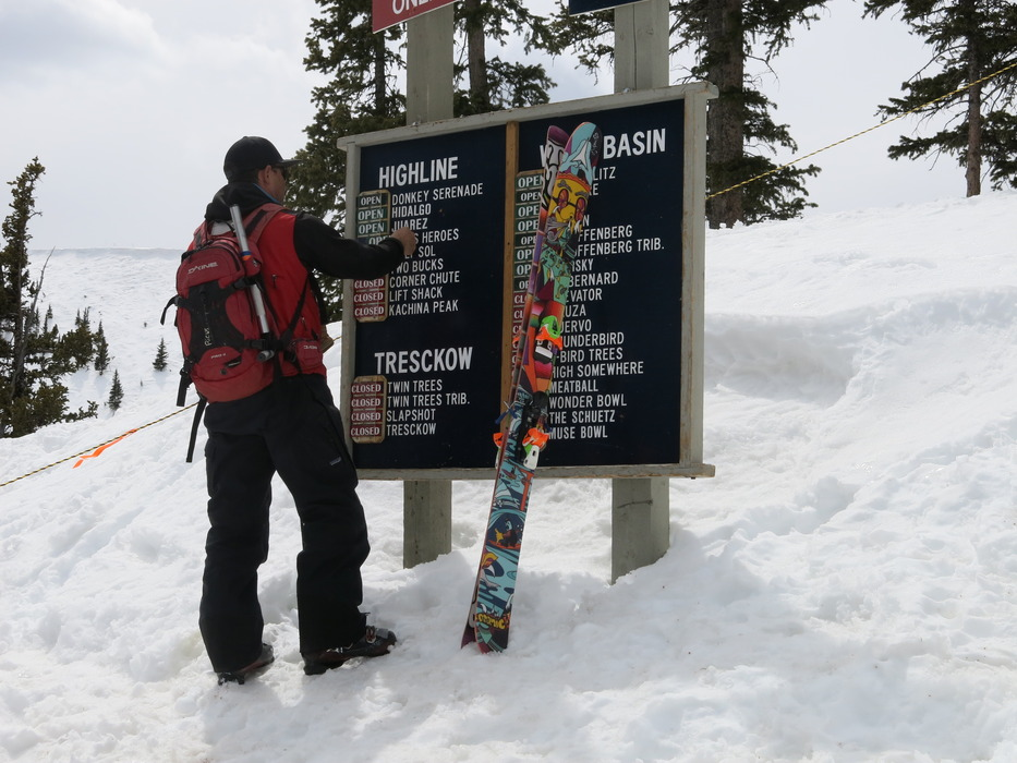 Patroller Ricus Ginn flipping signage at Taos Ski Valley.
