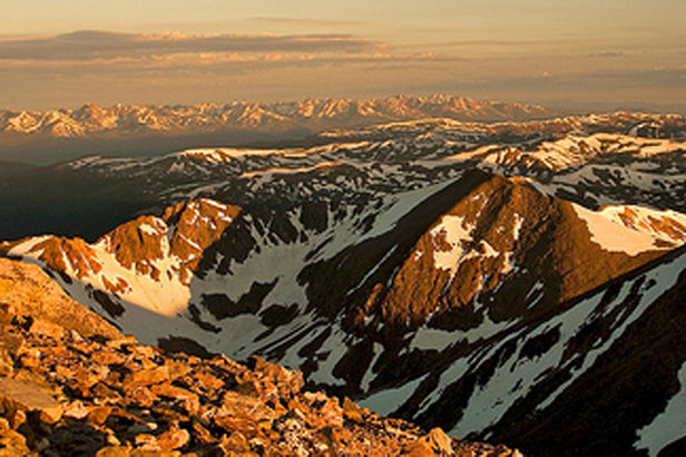 From Torreys Peak, the sunlight slowly exposes layers of snow-covered mountains across Summit County.  - ©Stephen Duncan
