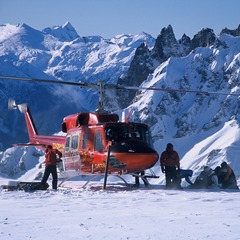 Heliskiing in Whistler. Helicopter unloading on a snowy mountain.