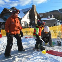 Burton Experience instructors push a young snowboarder on the LTR board. Photo Courtesy of Mountain Creek.