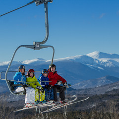 A family rides the lift on a bluebird day in New Hampshire. Photo Courtesy of Cranmore Mountain Resort.