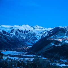 A nearly full moon shines down upon the Mountain Village and Town of Telluride.