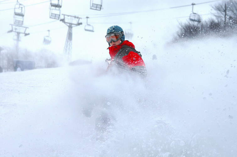 Snowboarding in deep powder at Beech Mountain Resort, NC. Photo Courtesy of Ski Beech.