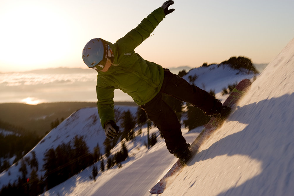 This snowboarder goes down the mountain early in the morning at Alpine Meadows, California