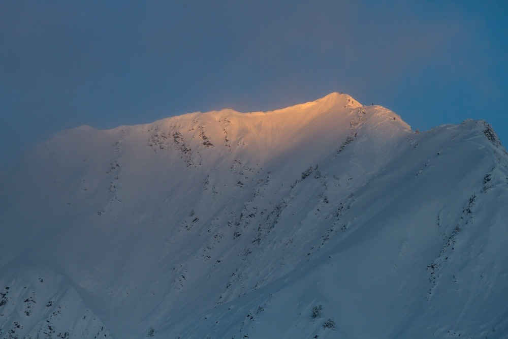 Morning light breaks on Mt Superior as dawn patrol skiers crest the summit. Photo by Liam Doran