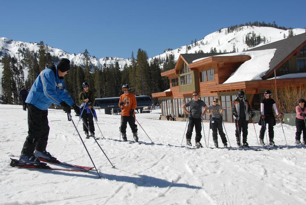 Taking a ski lesson at bottom of slopes