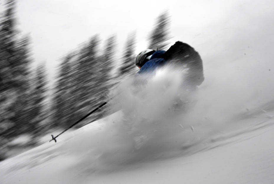 Skier flying through powder at Telluride, CO.