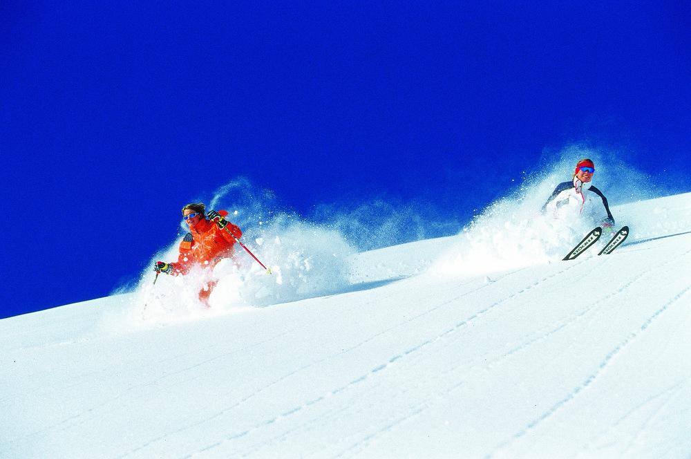 Skiers in thick powder at Hochfugen, AUT.