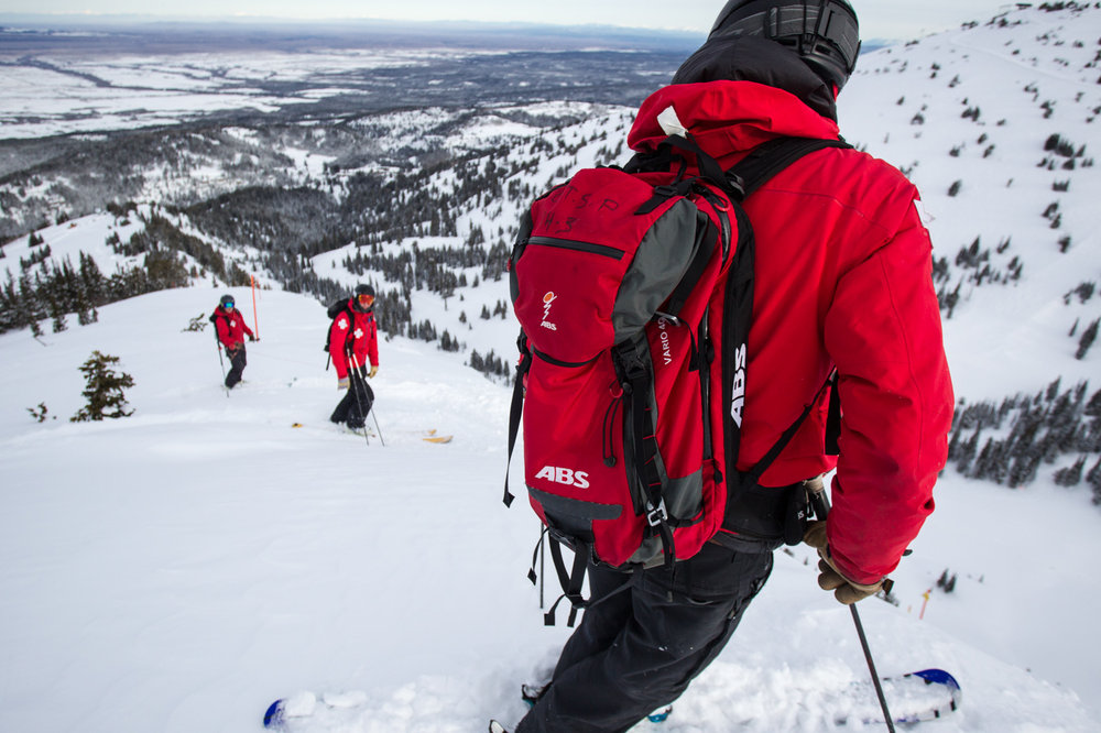Calder relays the plan as the patrol team prepares to ski cut the steepest open terrain on Peaked Mountain. - © Cody Downard Photography