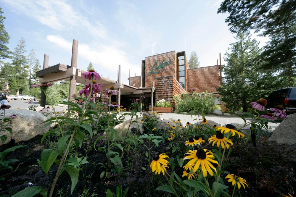 The exterior front of the Bear Valley Lodge with flowers in the foreground.