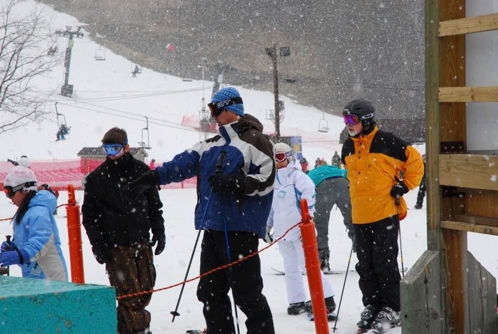 Skiers under falling snow at Boston Mills on Valentine's Day Weekend.
