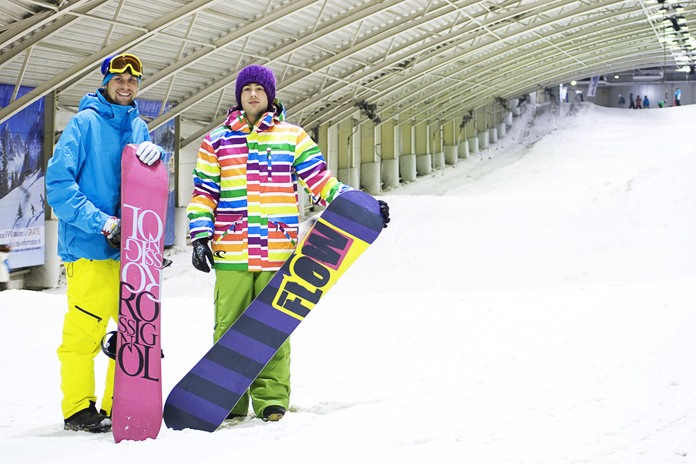 A pair of colorful snowboarders at SnowPlanet, Netherlands.