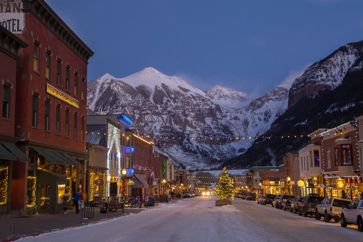 Main street Telluride looks festive over the holidays decked with garland and white lights. - © Visit Telluride/Ryan Bonneau