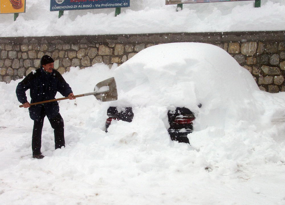 Man shoveling snow at Foppolo, Italy.