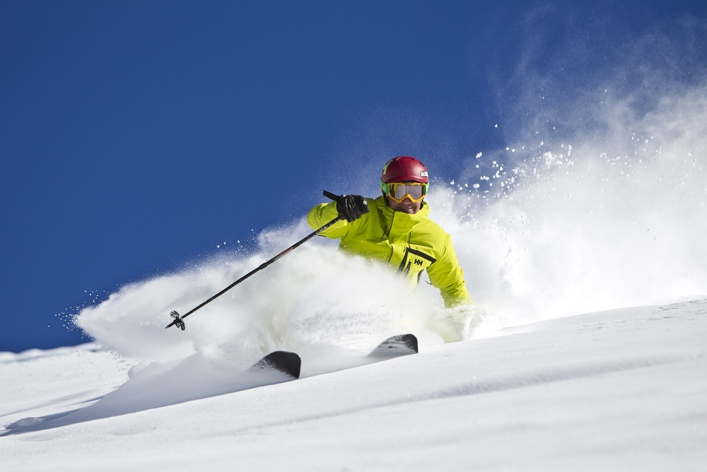A skier enjoys fresh powder and blue skies at Vail.