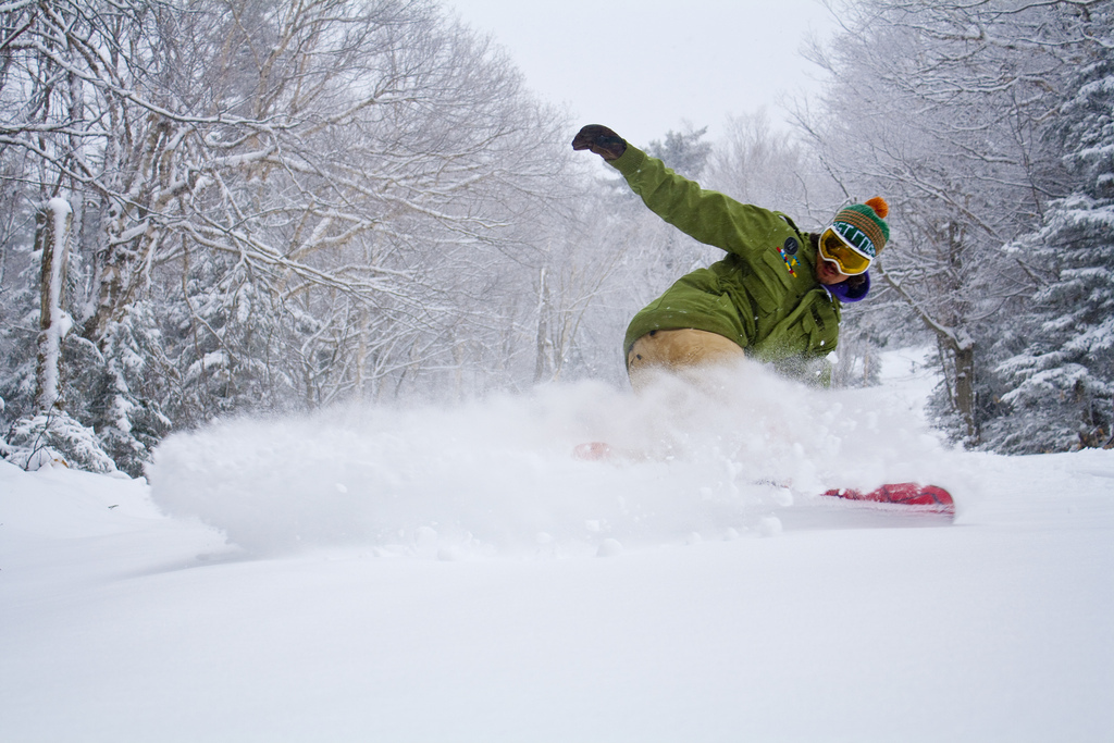 A snowboarder slashes a fresh layer of pow at Mount Snow. Photo Courtesy of Mount Snow. - ©Mount Snow