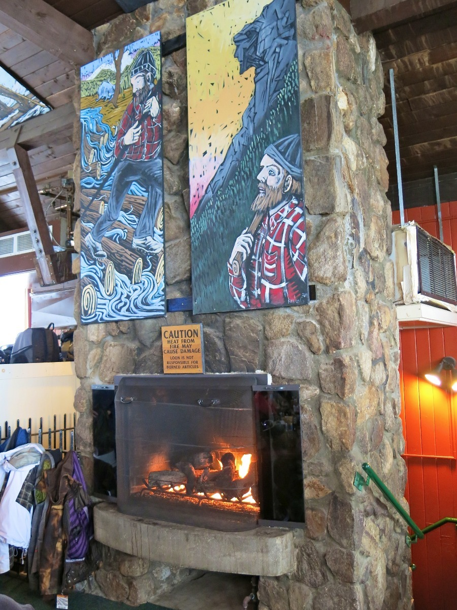 The roaring fire at the Paul Bunyan Room, complete with paintings of the Tall Tale Hero above. - © Donny O'Neill