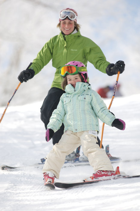 A mother follows closely behind her daughter at Mount Sunapee