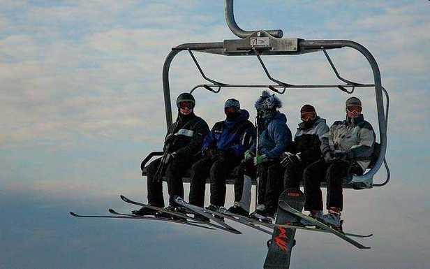 Skiers make their way up the mountain in a chairlift in Blue Mountain, Ontario