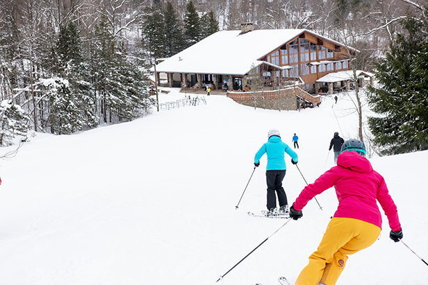 Skiers heading down Champagne to the Yodeler Lodge