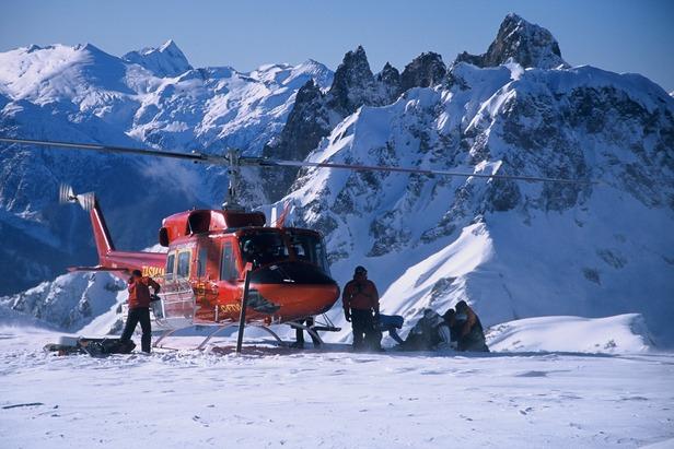 Vrtuľník vysadzuje lyžiarov na zasneženom svahu.